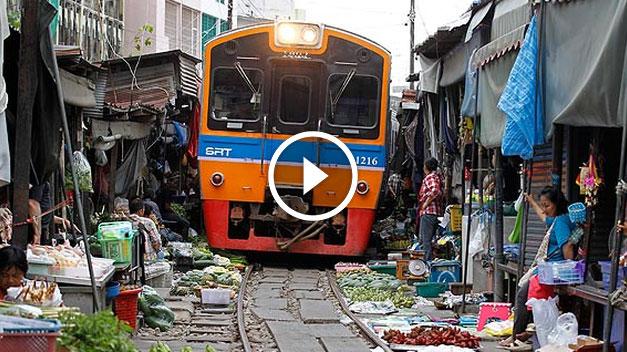 unbelievable train runs trough vegetable market in thailand